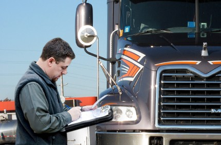 Man with clipboard in front of truck