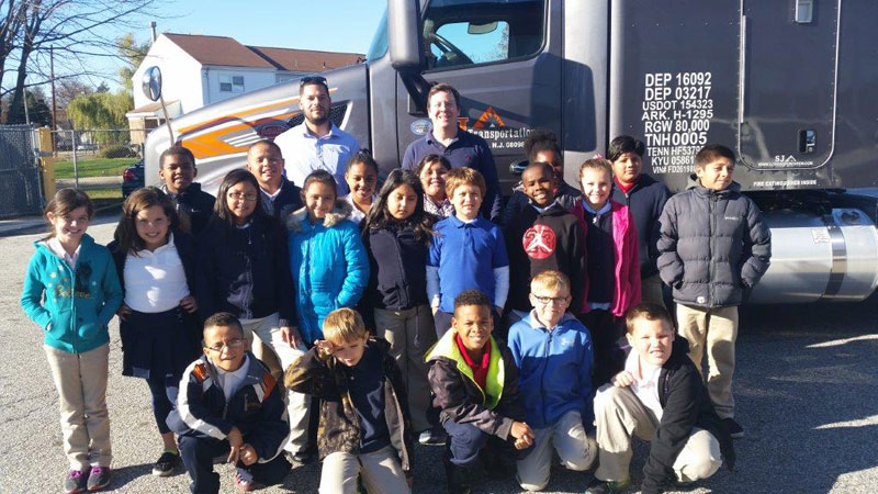 Group of kids standing in front of SJ Transportation truck