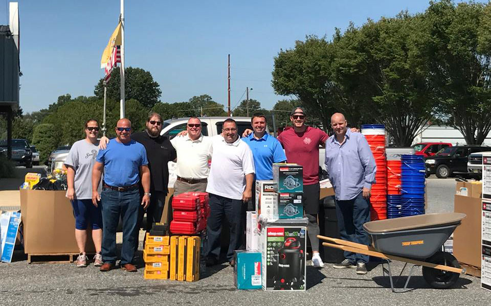 Group standing with donated goods for Hurricane Harvey relief