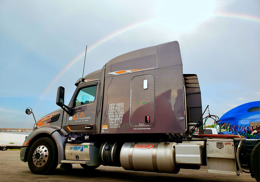 Truck with rainbow arching over it
