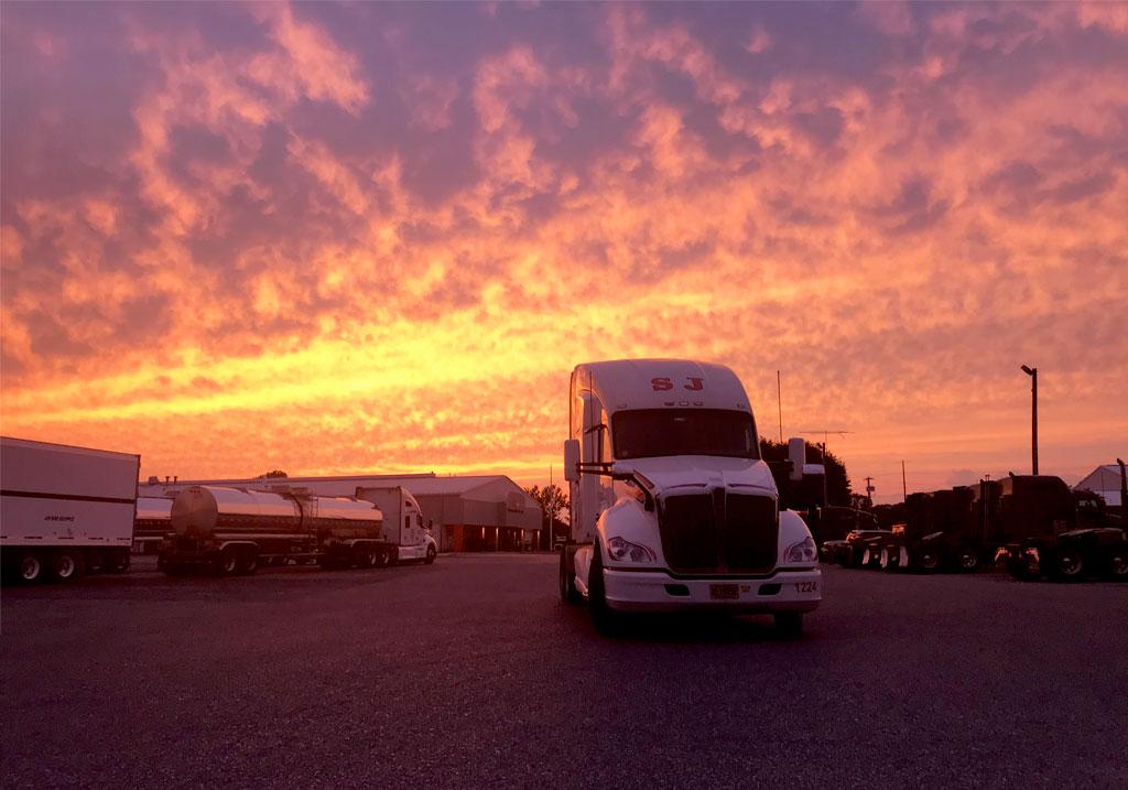 Truck at truck yard with magenta and yellow sunset